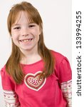 Young Caucasian girl in a multicolored heart shirt and smiling - stock photo
