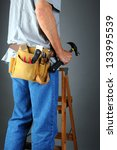 Closeup of a contractor standing on a wooden ladder holding his hammer. Vertical format over a light to dark gray background. Man is unrecognizable. - stock photo