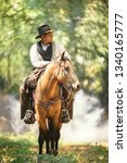 cowboy with his purebred horse standing in the forest  - stock photo