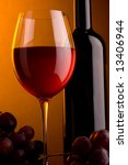 a glass of red wine and a bottle and grape - stock photo