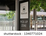 Small photo of Ride share sign with a picture of a car in a box. Black and white sign. Green leaves on a tree widows and a metal fence in the background . Also has pick-up zone on the bottom