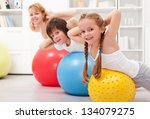 Kids exercising with their mother at home - stock photo