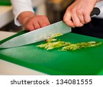 Chef chopping leek over green carving board. - stock photo