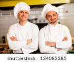 Two smart and confident smiling male chefs posing with arms crossed. - stock photo