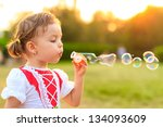 little girl blowing soap bubbles | Shutterstock . vector #134093609