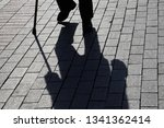 Small photo of Silhouette of man walking with a cane, long shadow on pavement. Concept of lame or blind person, disability, old age, poverty, diseases of the spine
