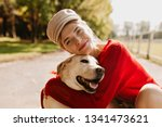 Stock photo charming girl and her dog having good time in the autumn park lovely blonde with beautiful dog 1341473621