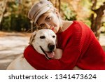 Stock photo lovely young girl in nice trendy red pullover hugging labrador in the forest pretty blonde in 1341473624