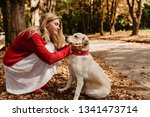 Stock photo young beautiful blonde in nice red sweater holding her white labrador tenderly in park pretty girl 1341473714