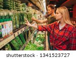 young couple in grocery store.... | Shutterstock . vector #1341523727