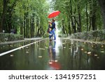 rain in the autumn park   young ... | Shutterstock . vector #1341957251