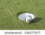 dollar on golf ball and hole