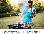 happy male preparing bbq meat | Shutterstock . vector #1342915841