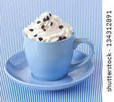 Cappuccino coffee with whipped cream in a blue cup. - stock photo