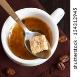 Cup of coffee and cube of brown sugar close up. - stock photo