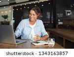 Stock photo smiling woman sitting in cafeteria holding coffee mug and working on laptop businesswoman checking 1343163857