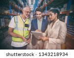 warehouse team discussing with... | Shutterstock . vector #1343218934