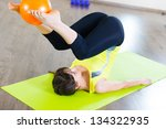 Pretty young girl fitness workout in gym with ball - stock photo