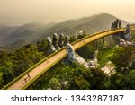 "Top aerial view of the famous Golden Bridge is lifted by two giant hands in the tourist resort on Ba Na Hill in Da Nang, Vietnam. "" Cau Vang"" is a favorite destination for tourists"