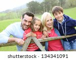 Family Leaning On A Fence In...