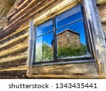 Wooden log cabin with window and a reflection of an other traditional log cabin and blue sky. Hamtland county, Duvberg, Sveg, Sweden