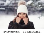 Small photo of Beautiful young girl in a winter knitted hat with a pompon. Close-up portrait of a girl in winter. Snow-covered model posing to the camera. The undeniable look of a woman.