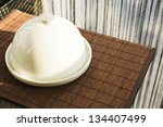Breakfast served composition: ceramic salver with white dish over glass table - stock photo