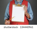 Closeup of a hardware store worker holding a clip board and pointing to it with a pencil. Man is unrecognizable. Horizontal format with a light to dark gray background. - stock photo