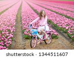 child riding bike in tulip... | Shutterstock . vector #1344511607