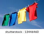Stock photo a set of primary colored t shirts hanging on a clothesline on a beautiful sunny day add text or 13446460