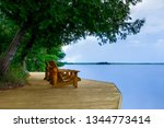 two adirondack chairs sitting... | Shutterstock . vector #1344773414