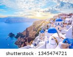 Small photo of Beautiful Oia town on Santorini island, Greece. Traditional white architecture and greek orthodox churches with blue domes over the Caldera, Aegean sea. Scenic travel background.