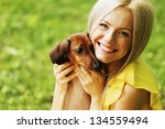 Stock photo woman dachshund in her arms on grass 134559494