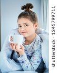 a little girl sirttiing on a... | Shutterstock . vector #1345799711