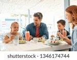 cheerful family in restaurant... | Shutterstock . vector #1346174744