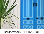 Blue door in Tunisia and palm tree - stock photo