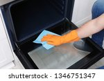 young man cleaning oven with... | Shutterstock . vector #1346751347