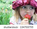 cute little girl in hat eating... | Shutterstock . vector #134703755