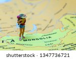 Miniature figurine concept : The young traveler traveling / standing on MONGOLIA in Asia map travel around the world, business trip traveler adviser agency or online world wide marketing concept.