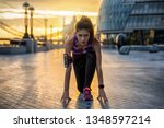 Beautiful female athelete in starter position ready to do her early morning workout at sunrise in the city