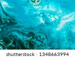 Abstract painting drawn by fluid acrylic technique. Picture with emerald, green, mint colorful water stains, gradients on blue background. Imitation of sea ocean waves on canvas. Modern art concept.
