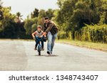 kid riding a bicycle while his... | Shutterstock . vector #1348743407