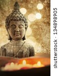 attractive textured picture of a Buddha figure with floating candles in a stone bowl - stock photo