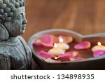 buddha head with stone heart, filled with water, rose petals and floating candles - stock photo