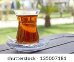 Glass with hot turkish tea on a sunny terrace - stock photo