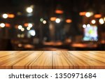 Stock photo empty wooden table top with blurred coffee shop or restaurant interior background abstract 1350971684
