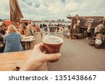 Craft beer glass in drinker hand on street food market of Copenhagen, Denmark. Leisure in Scandinavia with drinks and food of popular city market.