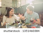 Small photo of Romantic dinner. Shameless long-haired girl stealing pieces of salad from plate of her confused male partner