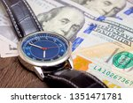 the watch is lying on dollars.... | Shutterstock . vector #1351471781