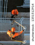 Workers installing scaffolding from above - stock photo